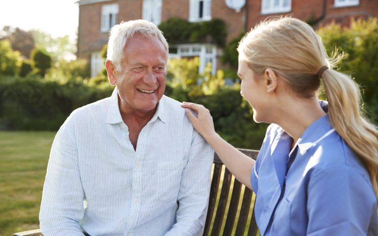 Nurse Talking To Senior Man In Residential Care Home